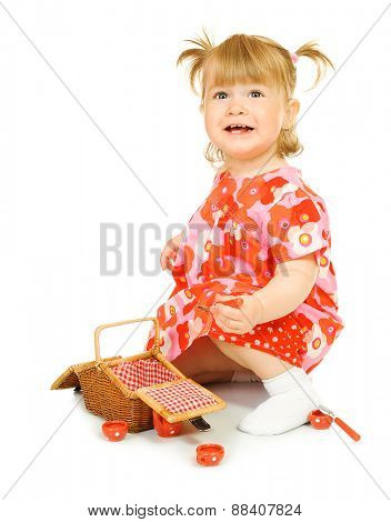 Small smiling baby in red dress with toy basket isolated