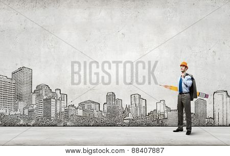 Young man engineer with huge pencil in hands and construction sketches at background