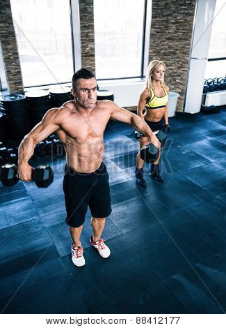 Muscular man and fit woman lifting dumbbells at gym