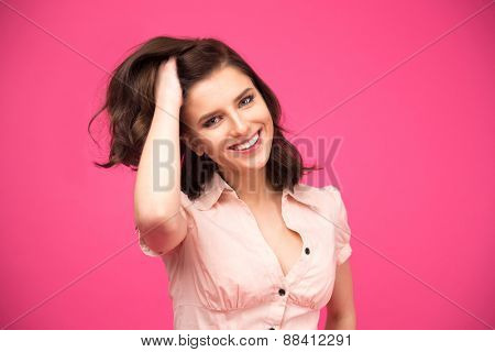 Happy woman touching her hair over pink background and looking at camera