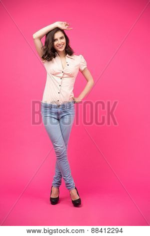 Full length portrait of a smiling young woman posing over pink background. Wearing in jeans and shirt. Looking at camera