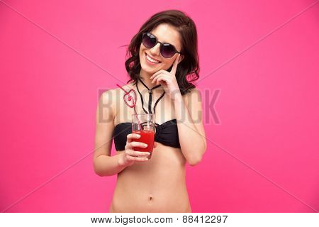 Cheerful woman in swimsuit holding glass of fresh juice over pink background