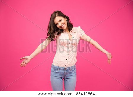 Portrait of a happiness young woman glad to see you over pink background