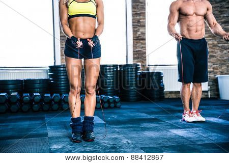 Man and woman workout with jumping rope at crossfit gym