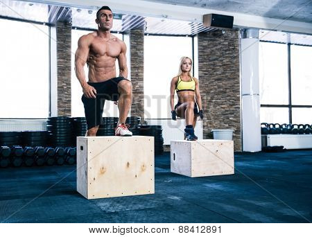 Group of man and woman working out with fit box at gym