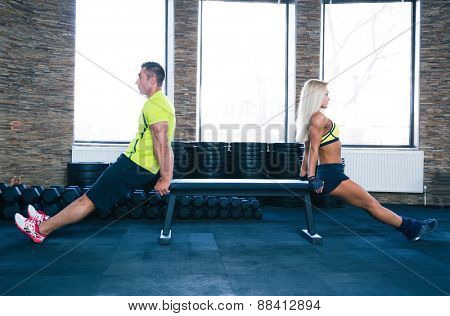 Woman and man doing exercises on hands with bench at gym