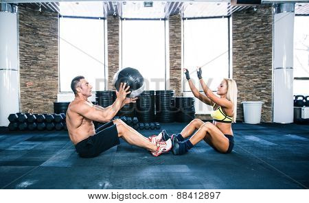 Group of a man and woman workout with fitball at gym