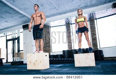 Group of man and woman workout with fit box at gym