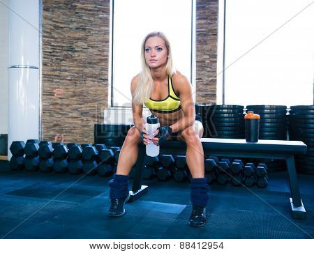 Beautiful sporty woman sitting on bench with bottle of water at gym and looking away