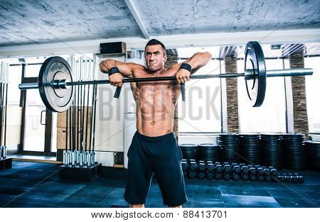 Handsome fitness man lifting barbell at gym