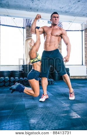 Fit woman hanging on a hand of muscular man at gym
