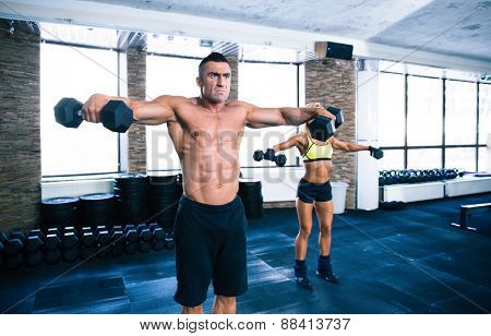 Muscular man and sporty woman lifting dumbbells at gym