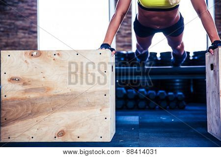 Fit woman doing push ups on fit box at gym