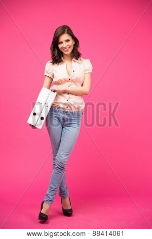 Full length portrait of a happy woman holding folders over pink background