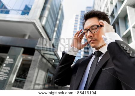 Businessman standing in street and trying to concentrate
