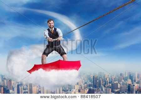 Businessman in umbrella on the cloud