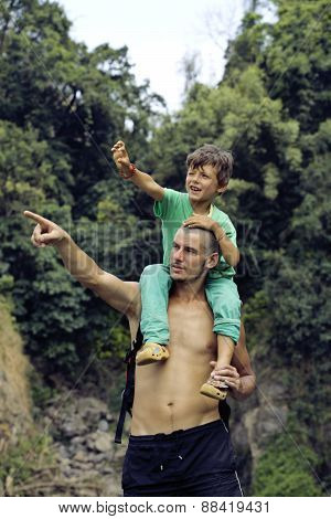 father and son making a trip to waterfall together, happy family