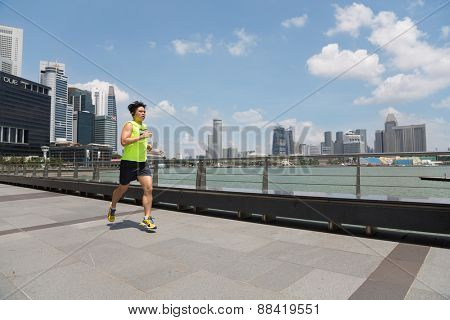 SINGAPORE - FEBRUARY 18, 2015: Young athlete running along the waterfront Marina Bay in Singapore. Quay Marina Bay a popular holiday destination and hanging out with locals and tourists.