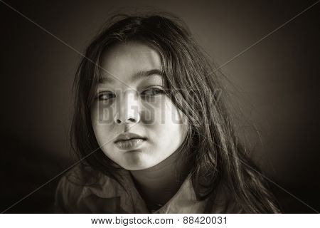 Black and white portrait of a sad little girl.