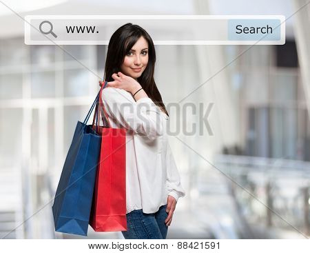 Young woman holding shopping bags in front of a search bar. Ecommerce concept