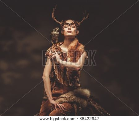 Woman shaman in ritual garment with hawk