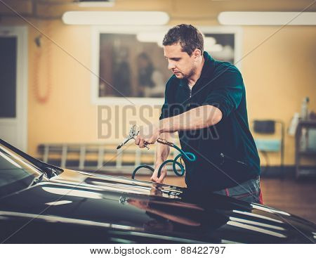 Man worker drying car on a car wash