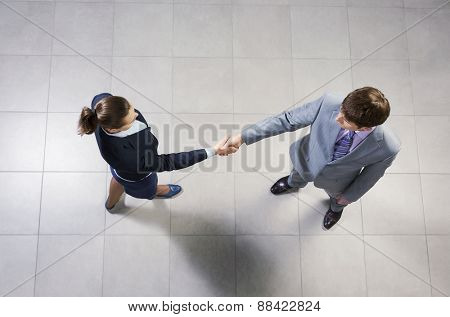 Top view of business partners shaking hands as a symbol of unity