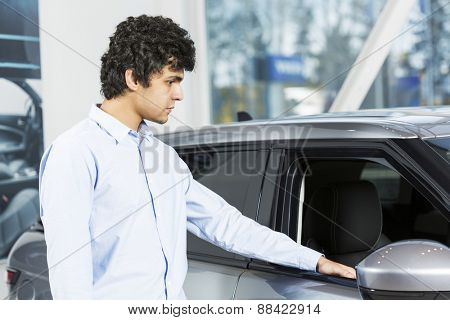 Handsome young man standing besides car in showroom