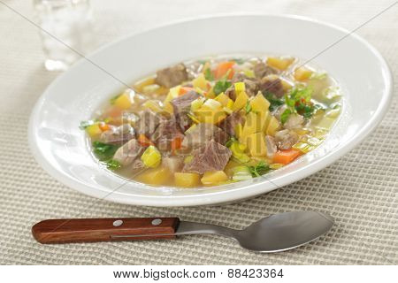Scotch broth soup in a white bowl closeup