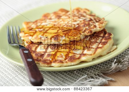Pancakes with pouring honey on a plate closeup. Selective focus on the honey