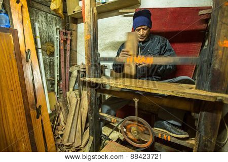 BHAKTAPUR, NEPAL - CIRCA DEC, 2013: Unidentified Nepalese man working in his wooden workshop. More 100 cultural groups have created an image of Bhaktapur as Capital of Nepal Arts.
