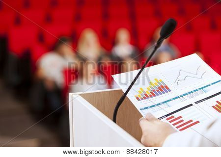 Businessman standing on stage and reporting for audience