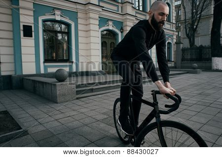 guy with beard in black clothes rides fix bike