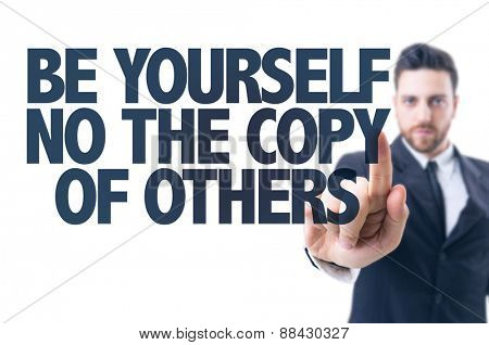 Business man pointing the text: Be Yourself Not The Copy of Others
