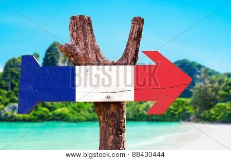 France Flag wooden sign with beach background