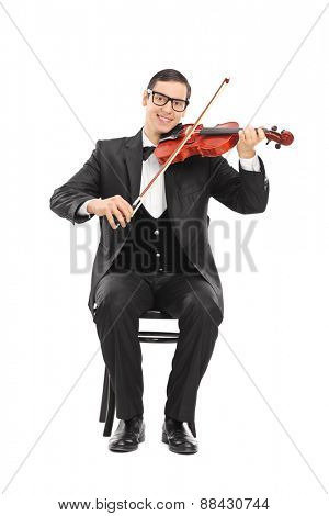 Cheerful young violinist playing an acoustic violin seated on a wooden chair isolated on white background