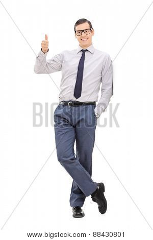 Full length portrait of a young elegant man giving a thumb up and looking at the camera isolated on white background