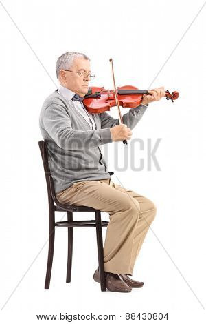 Senior musician playing an acoustic violin seated on a wooden chair isolated on white background