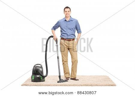 Young man posing next to a vacuum cleaner on a beige carpet isolated on white background