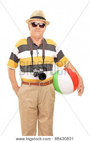 Vertical shot of a mature tourist with sunglasses and a camera holding a beach ball isolated on white background
