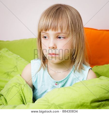 Portrait of upset 6 year old blond girl sitting in her bed with a chickenpox rash on her face