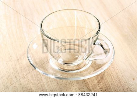 Transparent glass cup and saucer close-up