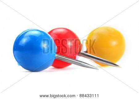 Three colorful round push pins on white background