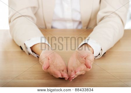Businesswoman presenting something in hands by a desk.
