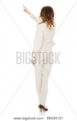 Businesswoman pointing up on space.