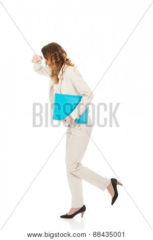 Tired businesswoman running with a binder.