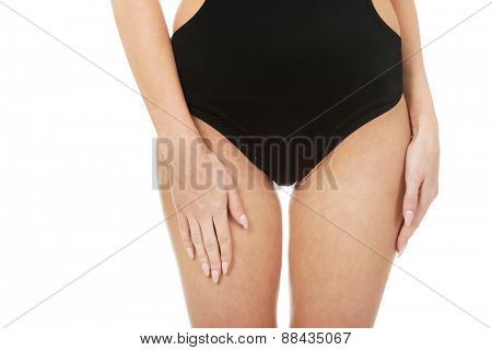 Beautiful slim woman's body in black swimsuit.