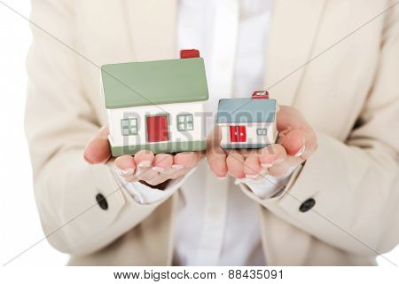 Businesswoman compares two house models in hands.