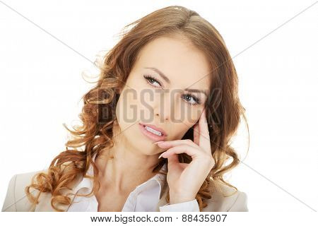 Pensive businesswoman looking up and touching chin.