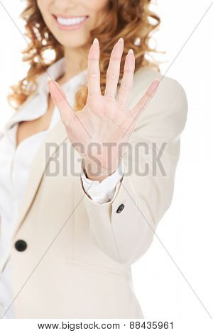 Smiling businesswoman showing hand to camera.